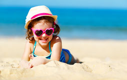 Happy child girl in bikini on beach in summer sea. Happy child girl in bikini on the beach in the summer sea Royalty Free Stock Photography