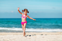 Happy child girl in bikini running on beach in summer sea. Happy child girl in bikini running on the beach in the summer sea Stock Image