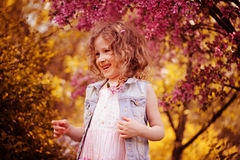 Happy child girl at blooming cherry tree in spring garden Royalty Free Stock Photos