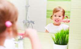 Happy child girl brushing her teeth toothbrushes in bathroom Stock Photography