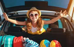 Happy child girl in car going on summer vacation trip stock images