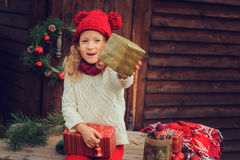 Happy child girl celebrating christmas outdoor at cozy wooden country house with gifts Royalty Free Stock Images