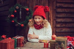 Happy child girl celebrating christmas outdoor at cozy wooden country house with gifts Stock Photography