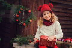 Happy child girl celebrating christmas outdoor at cozy wooden country house with gifts Stock Photo