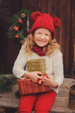 Happy child girl celebrating christmas outdoor at cozy wooden country house Stock Photography
