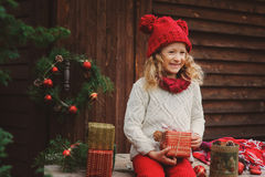 Happy child girl celebrating christmas outdoor at cozy wooden country house Stock Images