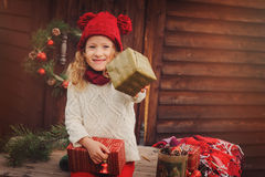 Happy child girl celebrating christmas outdoor at cozy wooden country house Stock Photo