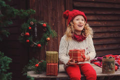 Happy child girl celebrating christmas outdoor at cozy wooden country house Royalty Free Stock Photo