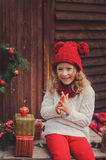 Happy child girl celebrating christmas outdoor at cozy wooden country house Stock Image