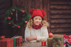 Happy child girl celebrating christmas outdoor at cozy wooden country house Royalty Free Stock Photos