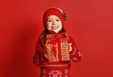 Happy child girl with christmas gift over red royalty free stock photography