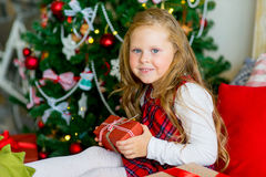 Happy child girl with Christmas gifts. Happy child girl with elf boots near a decorated Christmas tree surprized by Christmas gifts Royalty Free Stock Photos