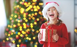 Happy child girl with christmas gifts near tree in morning royalty free stock photos