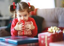 Happy child girl with christmas gifts near christmas tree in morning royalty free stock photos