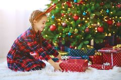 Happy child girl with christmas gifts near tree in morning stock images