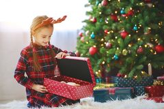 Happy child girl with christmas gifts near tree in morning stock photos