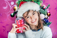 Happy child girl in a Christmas hat holding glass globe gift of Royalty Free Stock Images