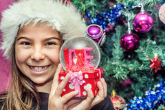 Happy child girl in a Christmas hat holding glass globe gift of. Love Stock Photos