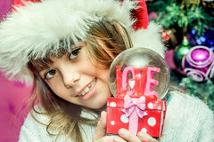 Happy child girl in a Christmas hat holding glass globe gift of. Love Stock Photography