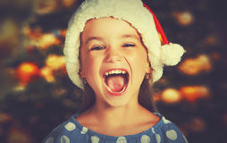 Happy child girl in a Christmas hat Stock Photos