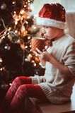 Happy child girl in Christmas hat and warm knitted socks drinking hot cocoa. Cozy festive scene with decorated tree on background Stock Photos