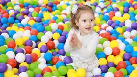 Happy child girl clapping hands and playing on the playground with multicolored balloons. Applause