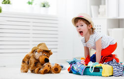 Happy child girl collect suitcase on vacation Royalty Free Stock Images