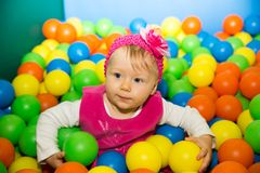 Happy child girl in colored ball on playground. Stock Photo