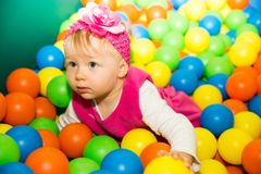 Happy child girl in colored ball on playground Royalty Free Stock Image