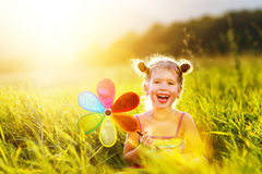 Happy child girl with colorful pinwheel windmill in summer Royalty Free Stock Images