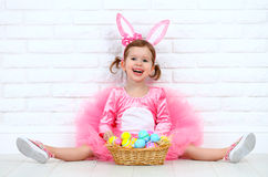 Happy child girl in a costume Easter bunny rabbit with basket of Stock Photos
