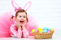 Happy child girl in a costume Easter bunny rabbit with basket of Stock Image