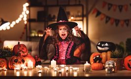 Happy child girl in costumes of witch in a dark house in hallow. Happy child girl in costumes of witch in a dark house in holiday Halloween royalty free stock photo