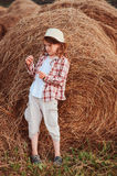 Happy child girl in country style plaid shirt and hat relaxing on summer field Stock Photos