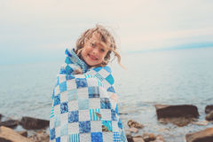 Happy child girl covered in quilt blanket, cozy summer holidays on seaside Stock Photography