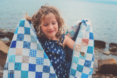 Happy child girl covered in quilt blanket, cozy summer holidays on seaside Royalty Free Stock Image