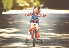 Happy child girl cyclist riding a bike. On the road Stock Image