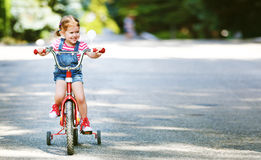 Happy child girl cyclist riding a bike Royalty Free Stock Images