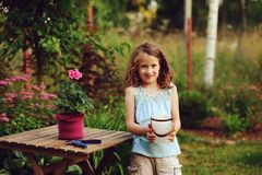 Happy child girl decorating evening summer garden with candle holder. Smiling kid helps on backyard on vacations Royalty Free Stock Photography