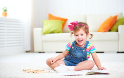 Happy child girl drawing with colored pencils lying on floor Royalty Free Stock Images