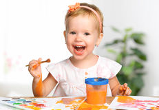 Happy child girl draws paints Royalty Free Stock Images
