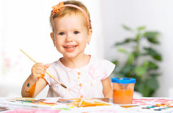 Happy child girl draws paints Royalty Free Stock Image