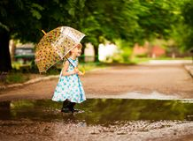 Happy child girl in dress with an umbrella and rubber boots in puddle on summer walk stock photos