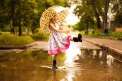 Happy child girl in dress with an umbrella and rubber boots in puddle on walk royalty free stock image