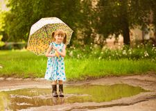 Happy child girl in dress with an umbrella and rubber boots in puddle on walk stock photography
