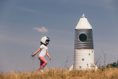 Happy child girl dressed in an astronaut costume playing with hand made rocket. Summer outdoor Royalty Free Stock Photos