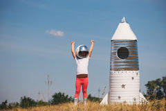 Happy child girl dressed in an astronaut costume playing with hand made rocket. Summer outdoor Royalty Free Stock Photo