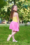 Happy child girl dressed in casual cloth posing, childhood concept, summer season in city park Royalty Free Stock Image