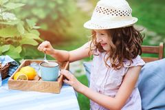 happy child girl drinking tea with lemons in summer garden Royalty Free Stock Images