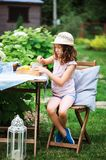 Happy child girl drinking tea with lemons in summer garden Stock Photography